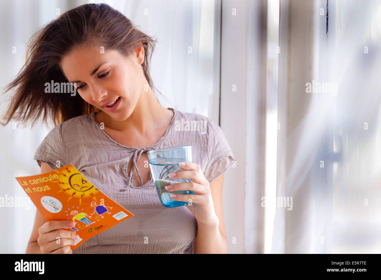 Woman consulting documentation on the heatwave. - Stock Image