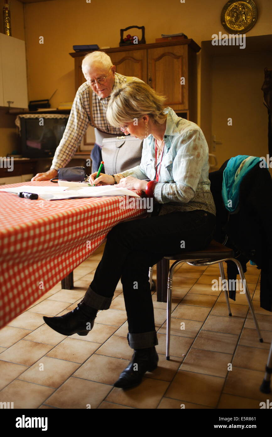 General practitioner writing a medical prescription during home visit. Stock Photo