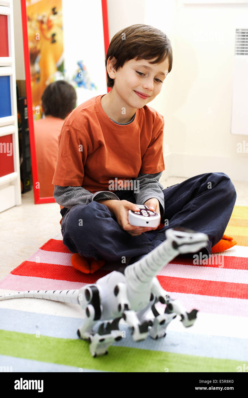 Chils playing with remote-controlled toy. - Stock Image