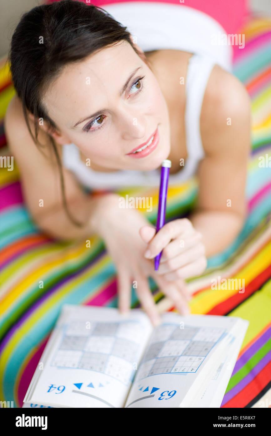 Woman playing sudoku. - Stock Image