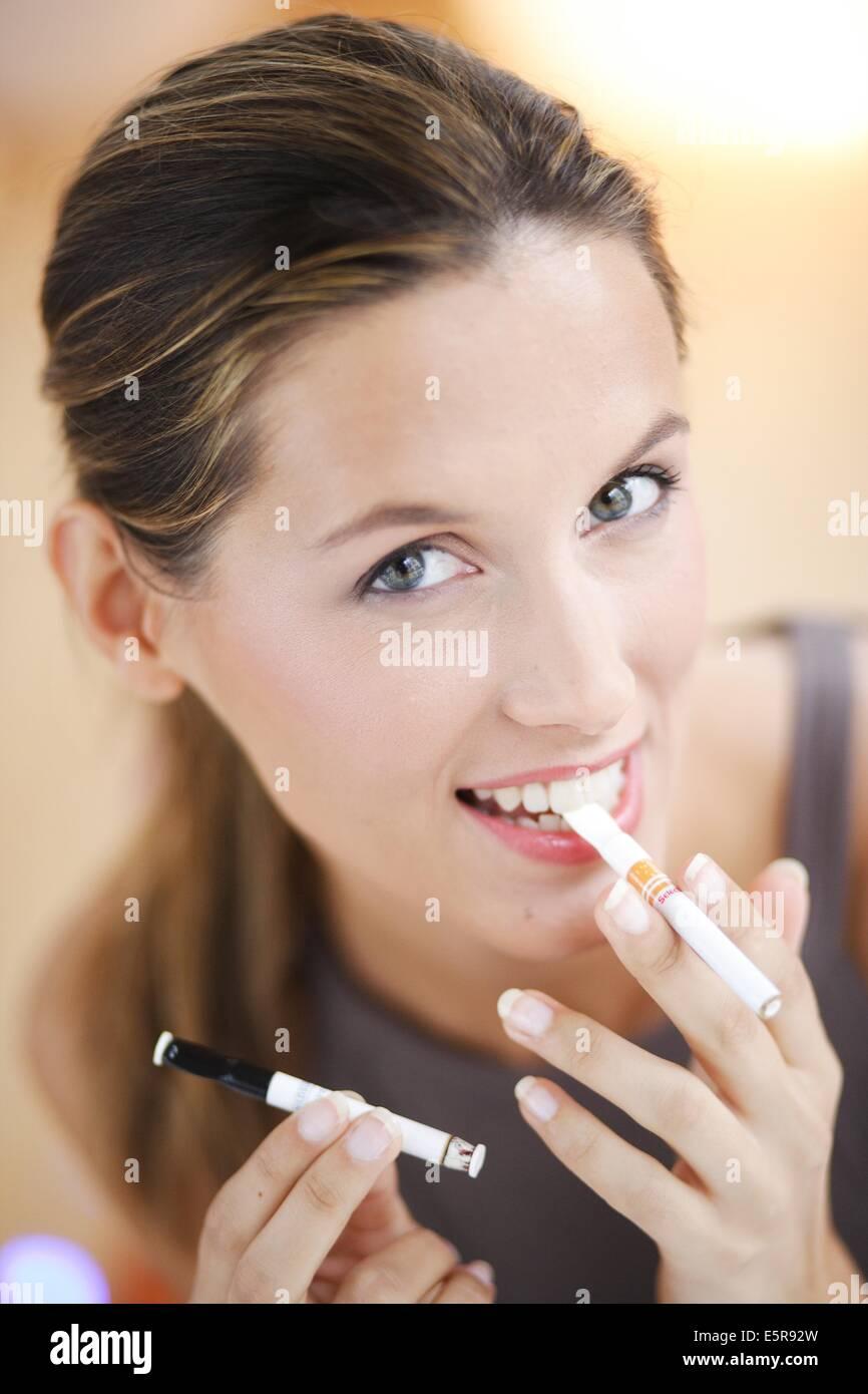 Woman smoking flavored nicotine-free cigarette. - Stock Image