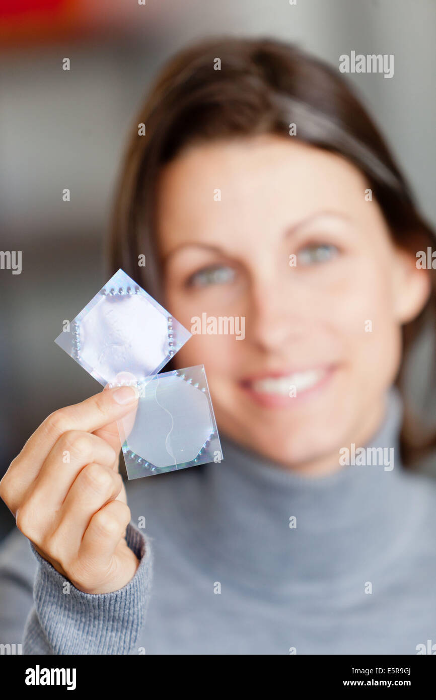 Woman use an oestrogen patch for a Hormone Replacement Therapy (HRT), in order to releive the undesirable effects - Stock Image