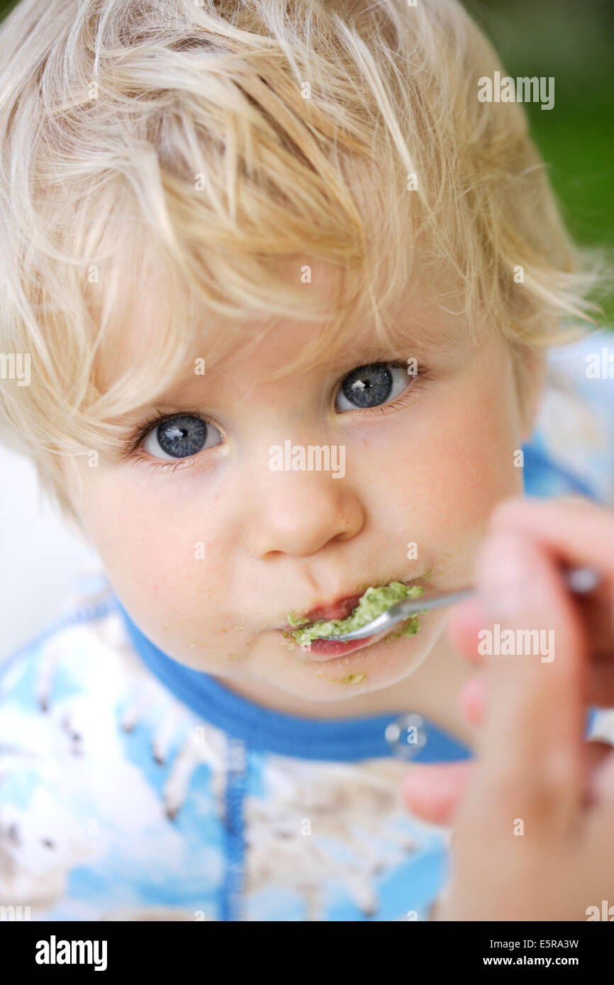 Parent spoon feeding 10 month old baby stock image