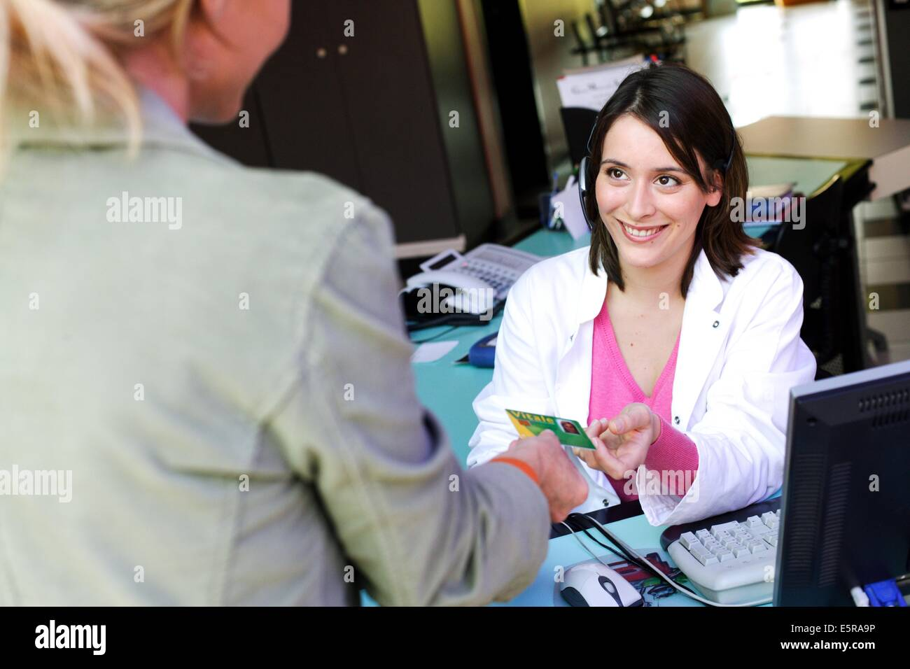 Woman giving a medical secretary her health card in a medical office. - Stock Image