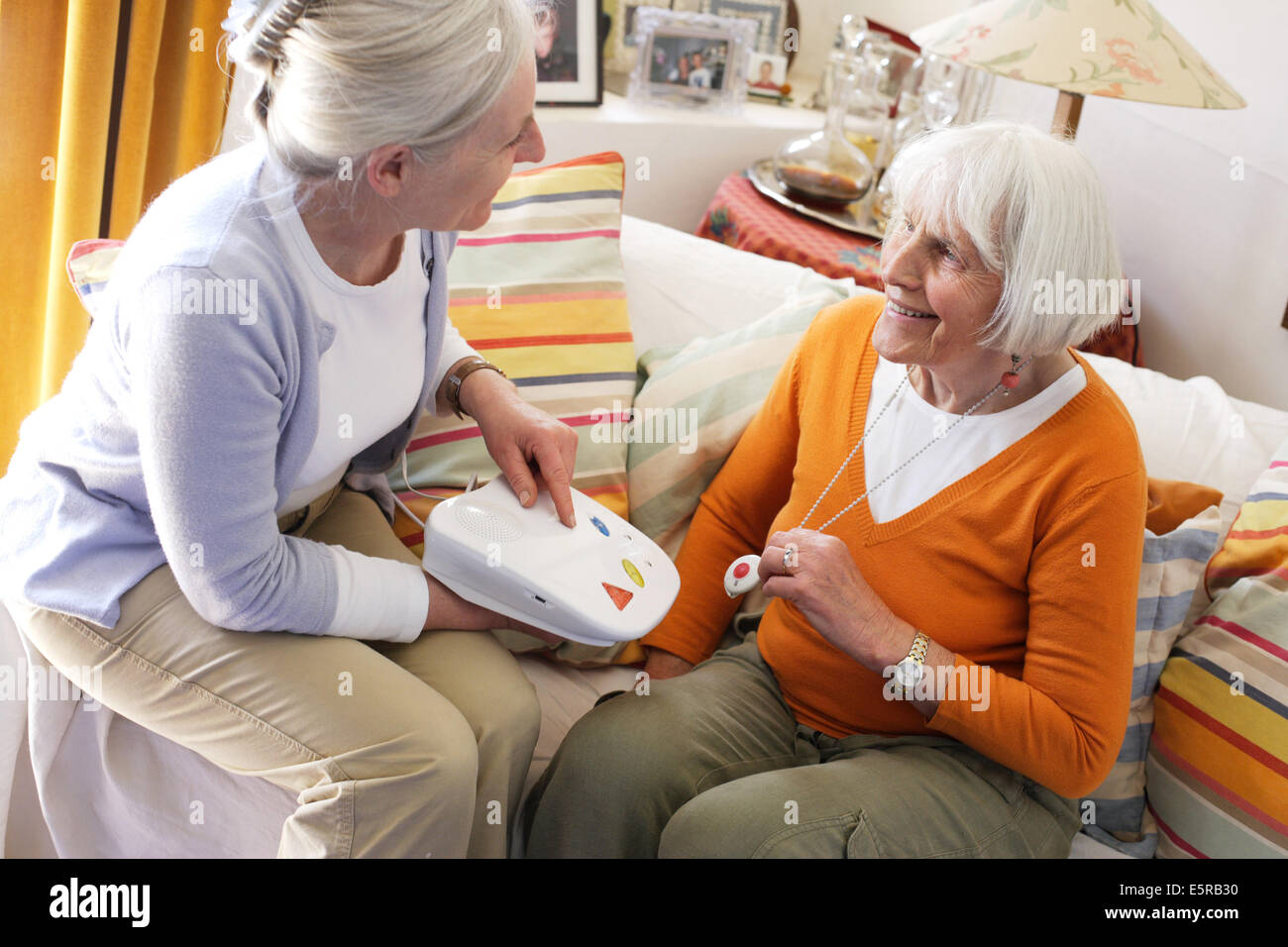 Emergency call button, elderly woman wearing a remote assistance unit at home. - Stock Image