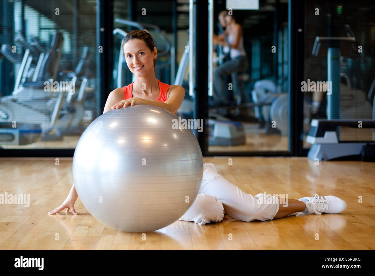 Woman with excercise ball in a gym. - Stock Image