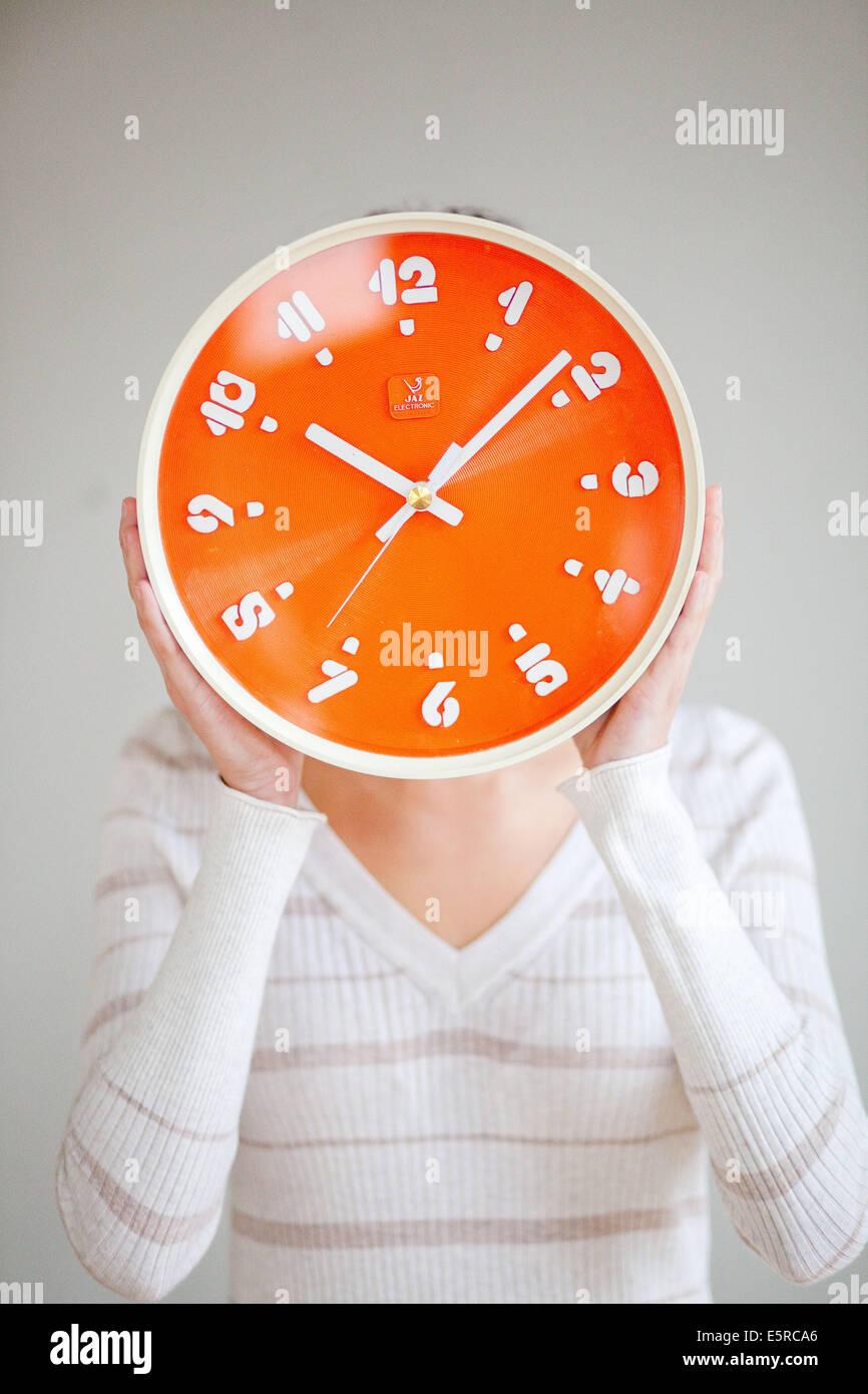 Woman holding orange clock. - Stock Image