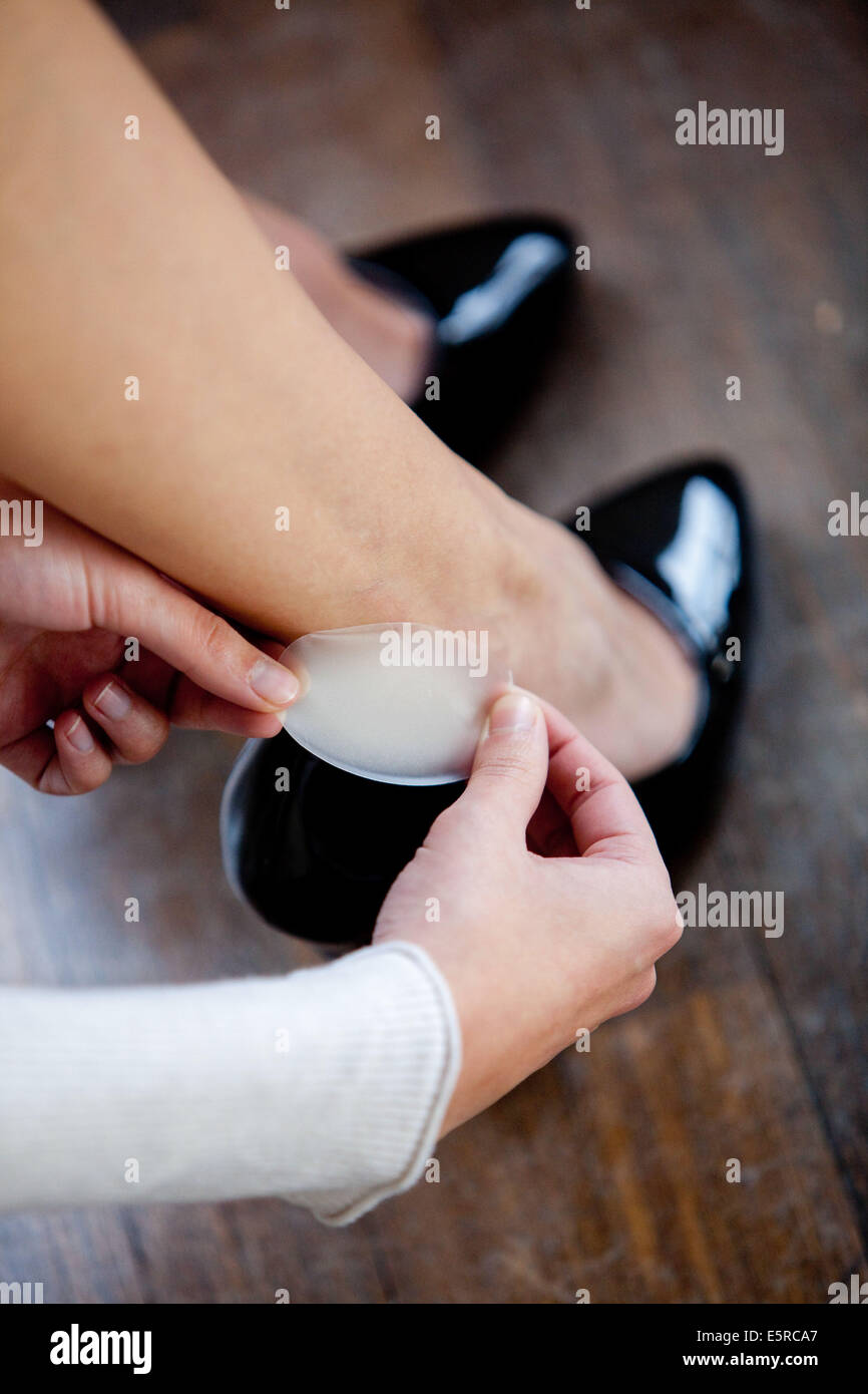 Woman putting a synthetic skin bandage on her heel. - Stock Image