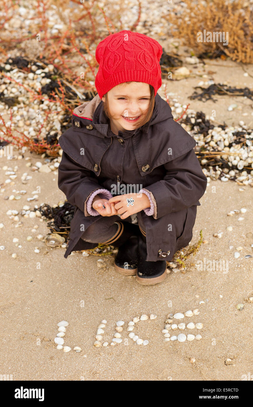 4 year old girl witth her first name written on the sand. - Stock Image