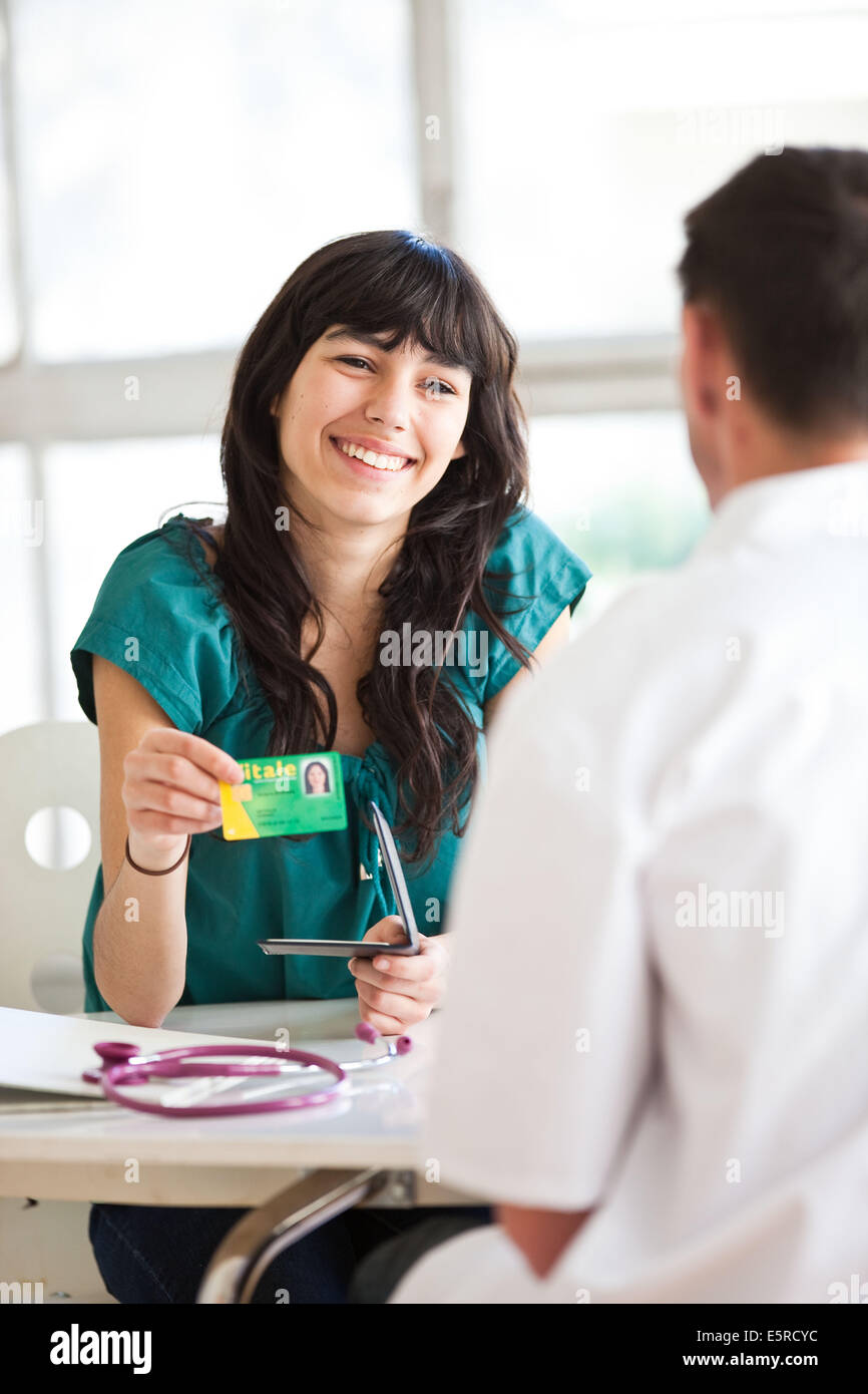 Teenage patient giving her social insurance identity card or health card (Carte Vitale) to the doctor after medical - Stock Image