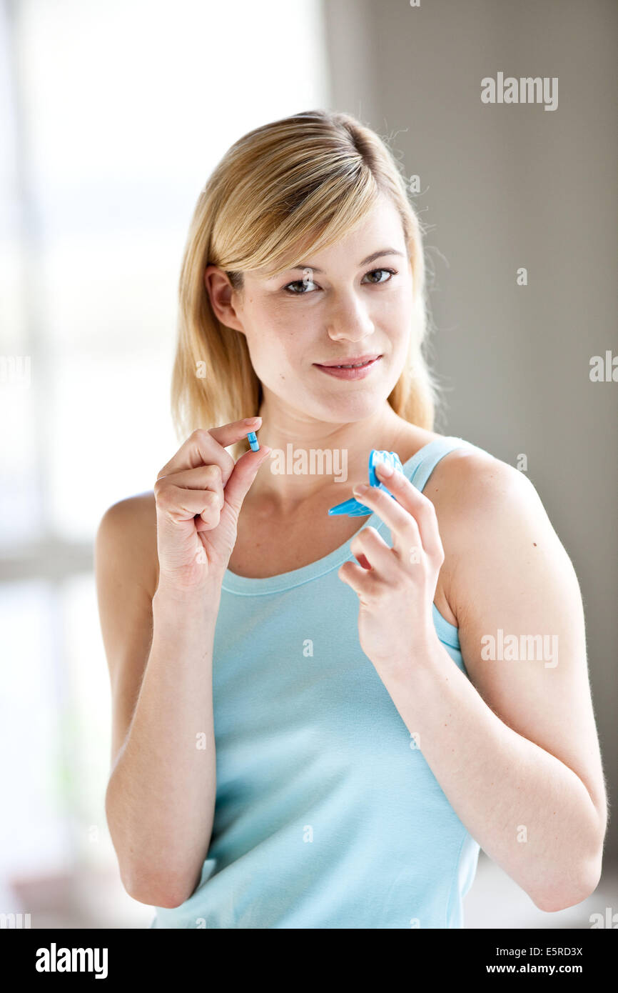 Woman taking Alli medicine, Alli is a half-dose version of the diet drug Xenical (Orlistat) produced by GlaxoSmithKline - Stock Image