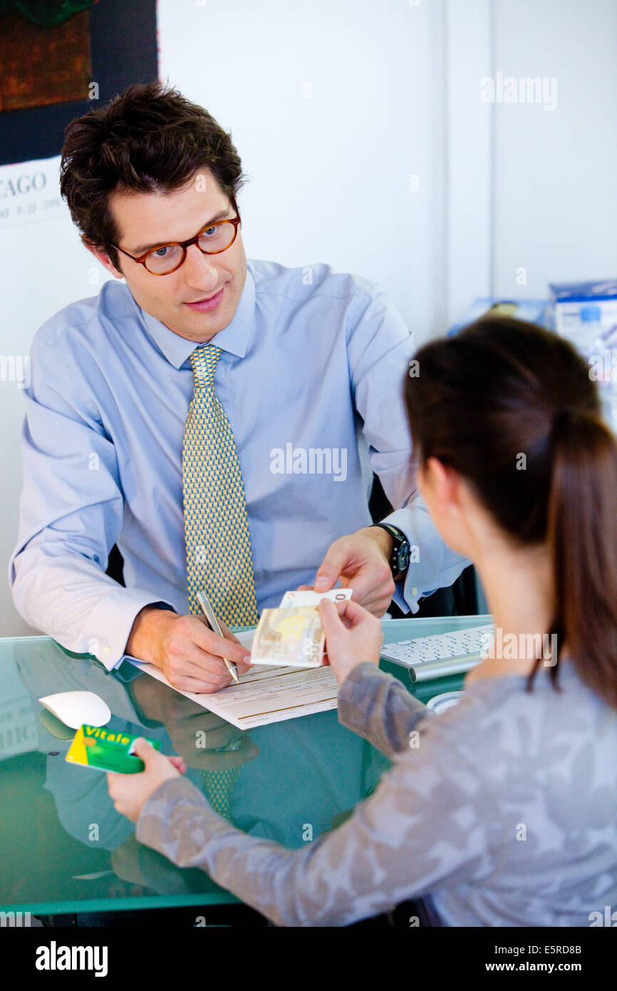 Patient using her health card (Carte Vitale) when paying consultation fees to doctor. - Stock Image