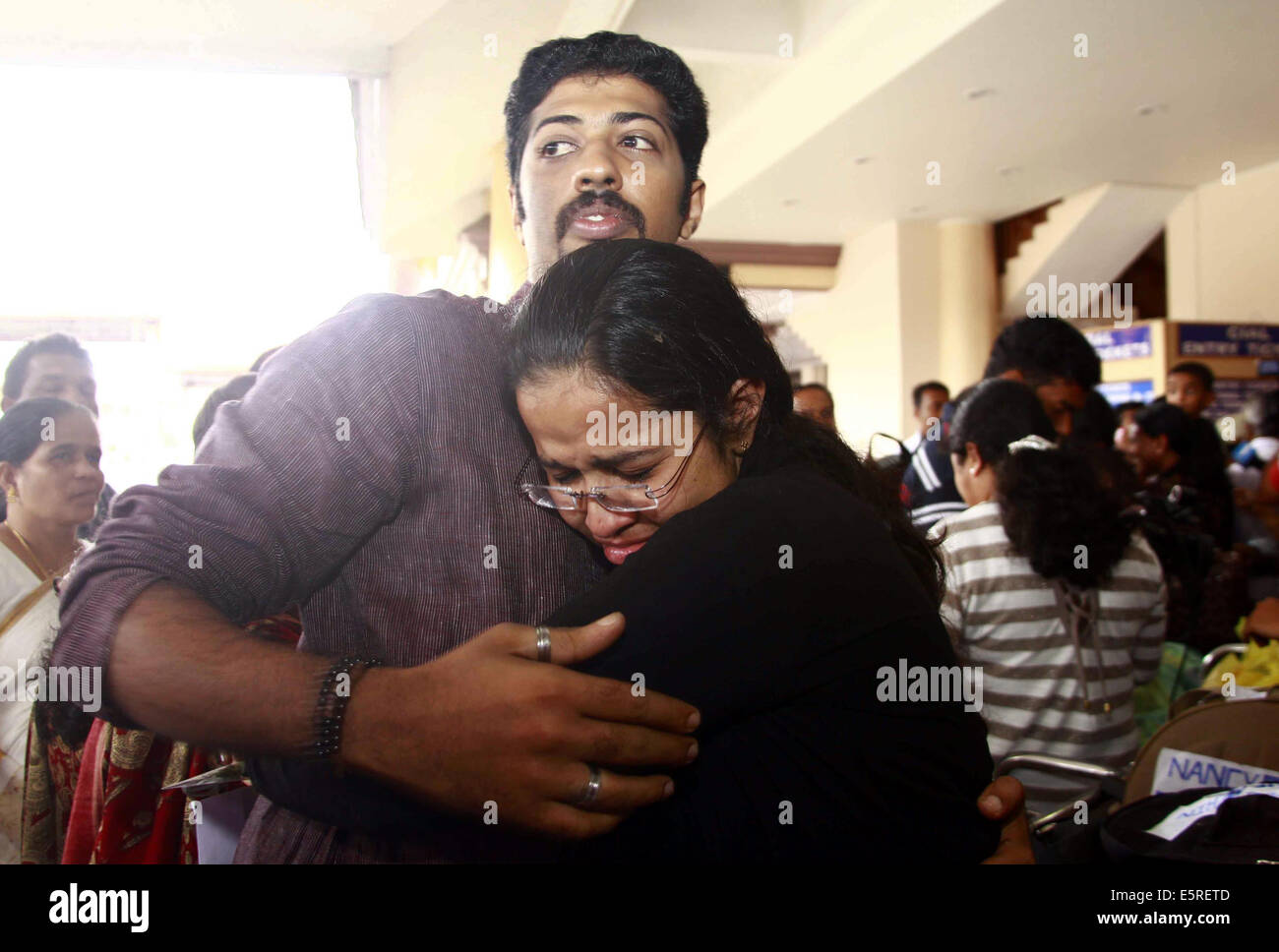 Kochi. 5th Aug, 2014. One of the 44 Indian nurses evacuated from war torn country Libya hugs her relative on her - Stock Image