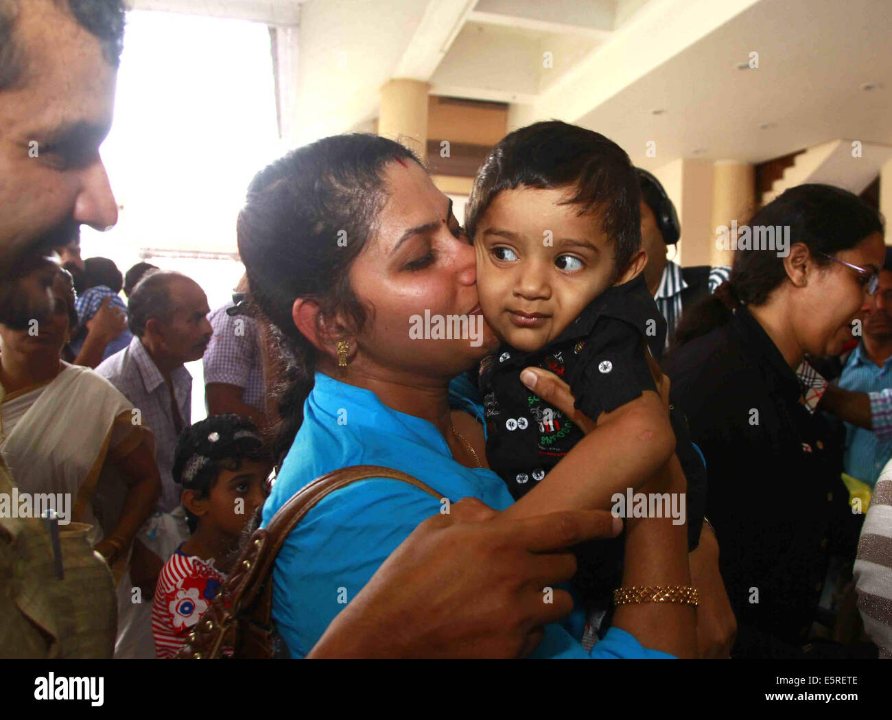 Kochi. 5th Aug, 2014. One of the 44 Indian nurses evacuated from war torn country Libya hugs her son on her arrival - Stock Image