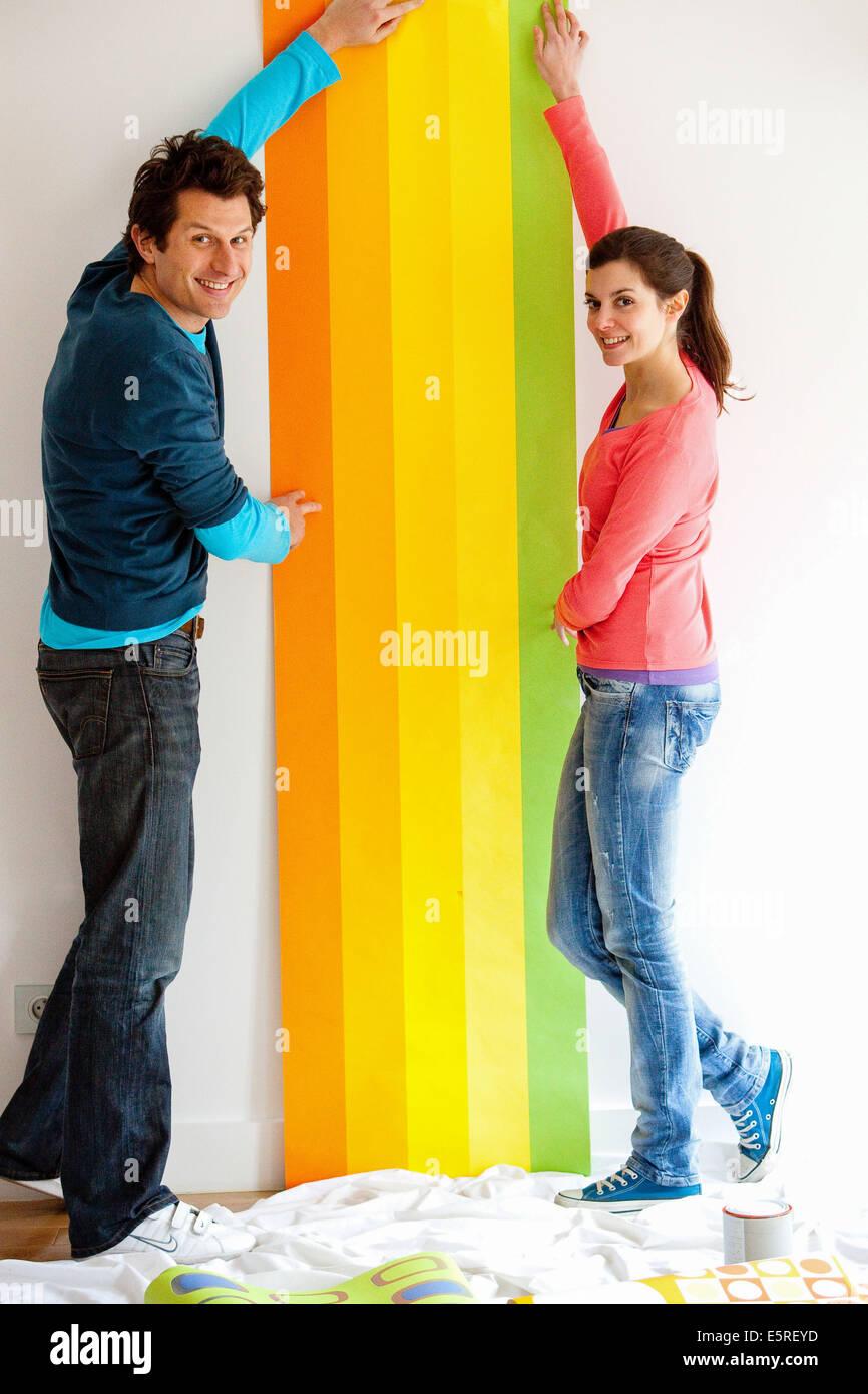 Couple putting wallpaper. - Stock Image
