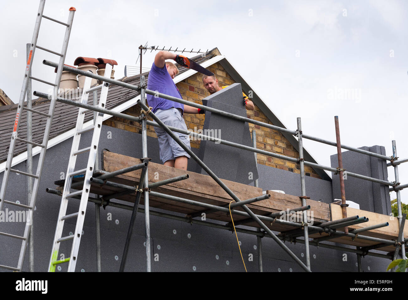 Builders attaching / fitting rigid foam wall insulation sheets / panels / boards to the gable end of Victorian terraced - Stock Image