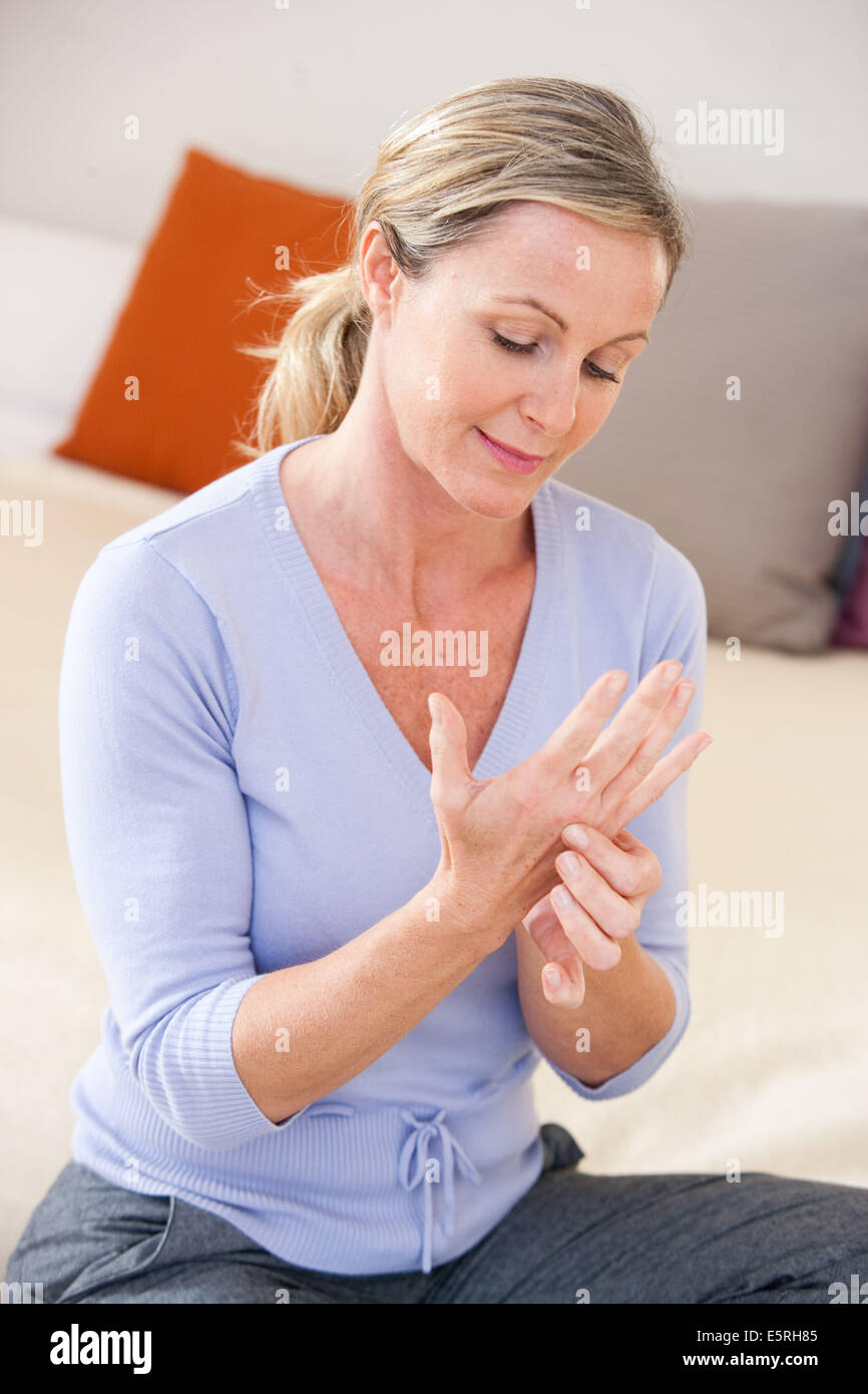 Woman suffering from hand pain. - Stock Image