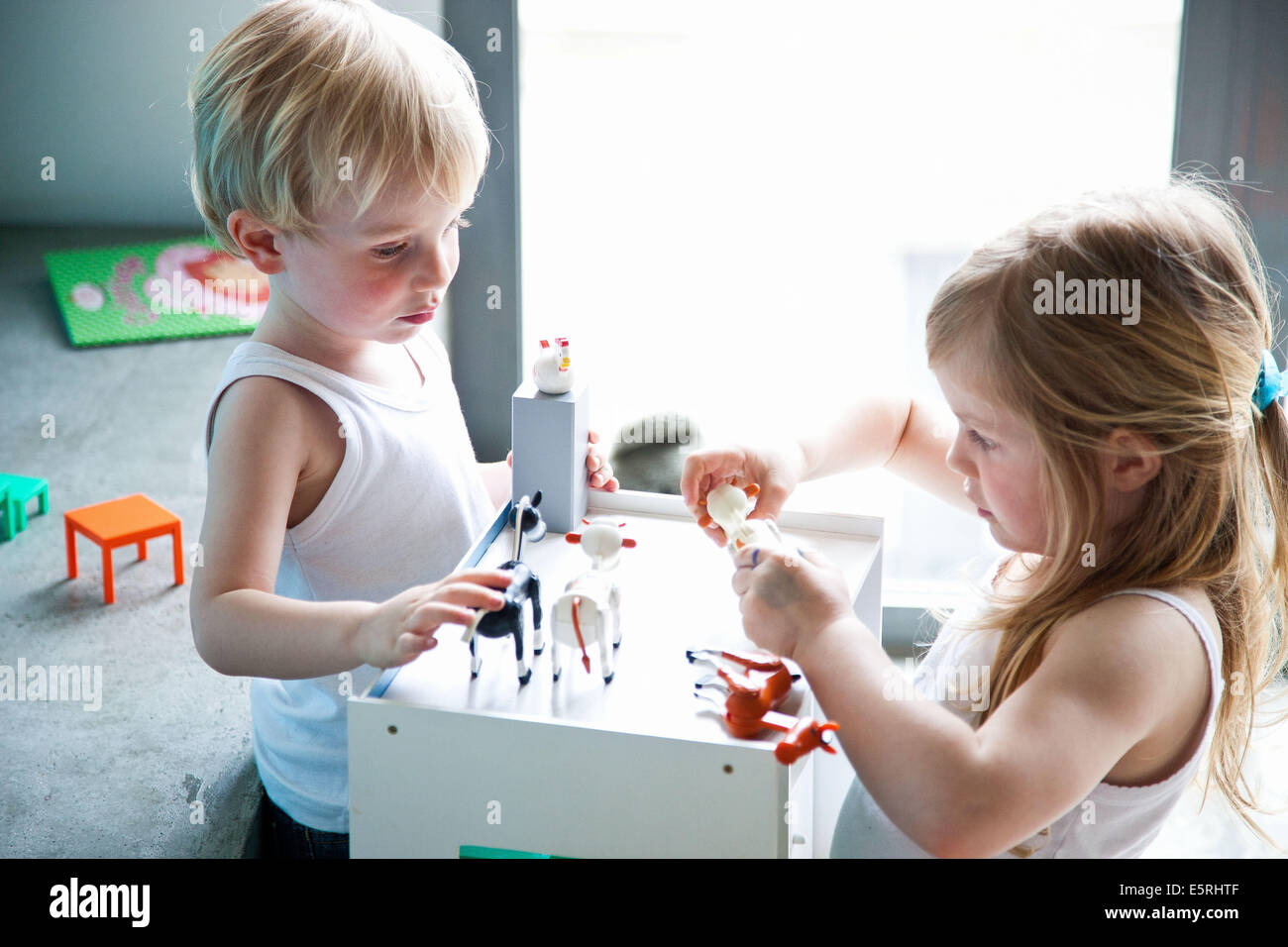 Brother and sister playing with figurines. - Stock Image