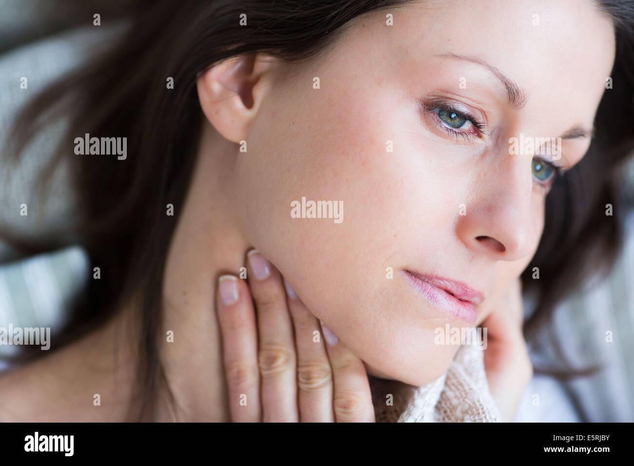 Sore throat. Woman stroking her throat. - Stock Image