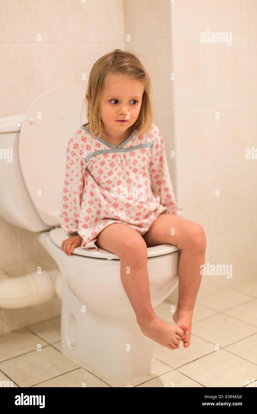 3 year old girl using an adult toilet having progressed from the use of a  child's potty.