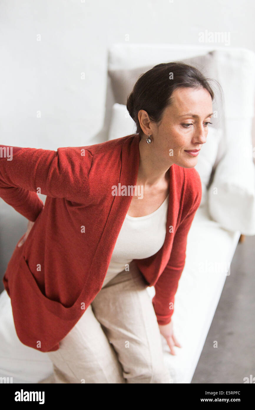 Woman suffering from back pain. - Stock Image