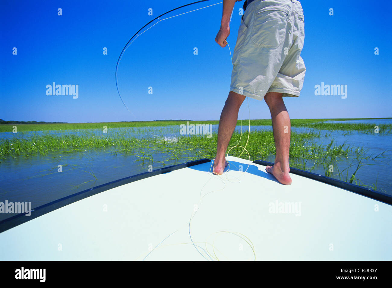 Fisherman reeling in catch, low section - Stock Image