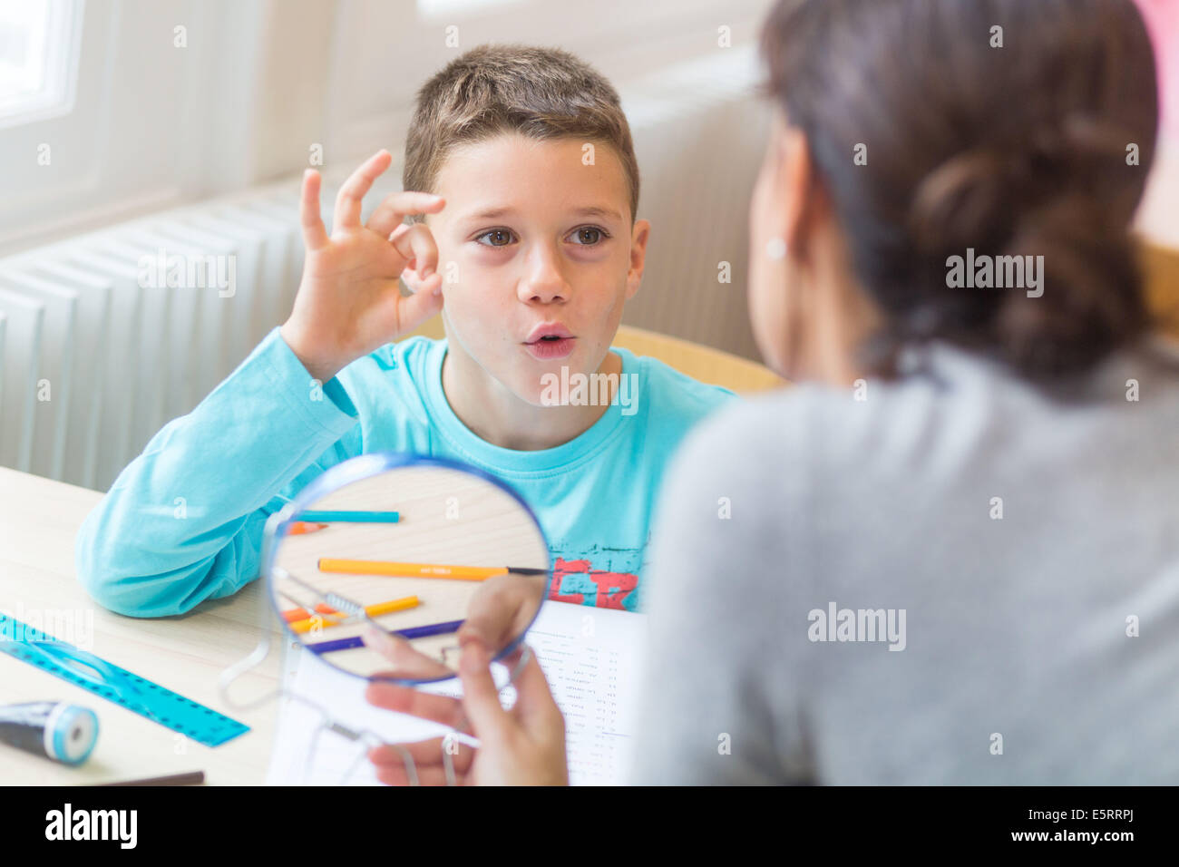 7 year old boy during speech therapy session. - Stock Image