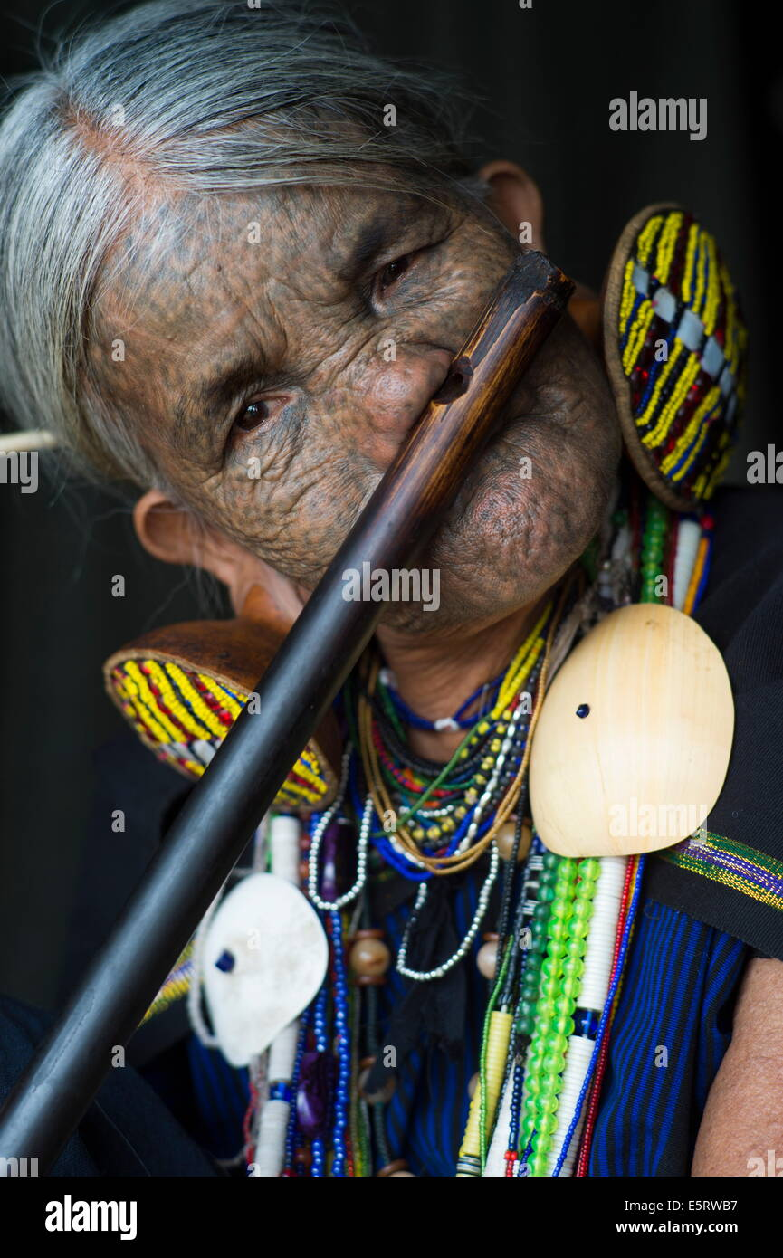 85-year old Chin woman (Yun Eian) playing nose flute, Mindat, Chin State, Myanmar. Her face is tattooed, traditional - Stock Image