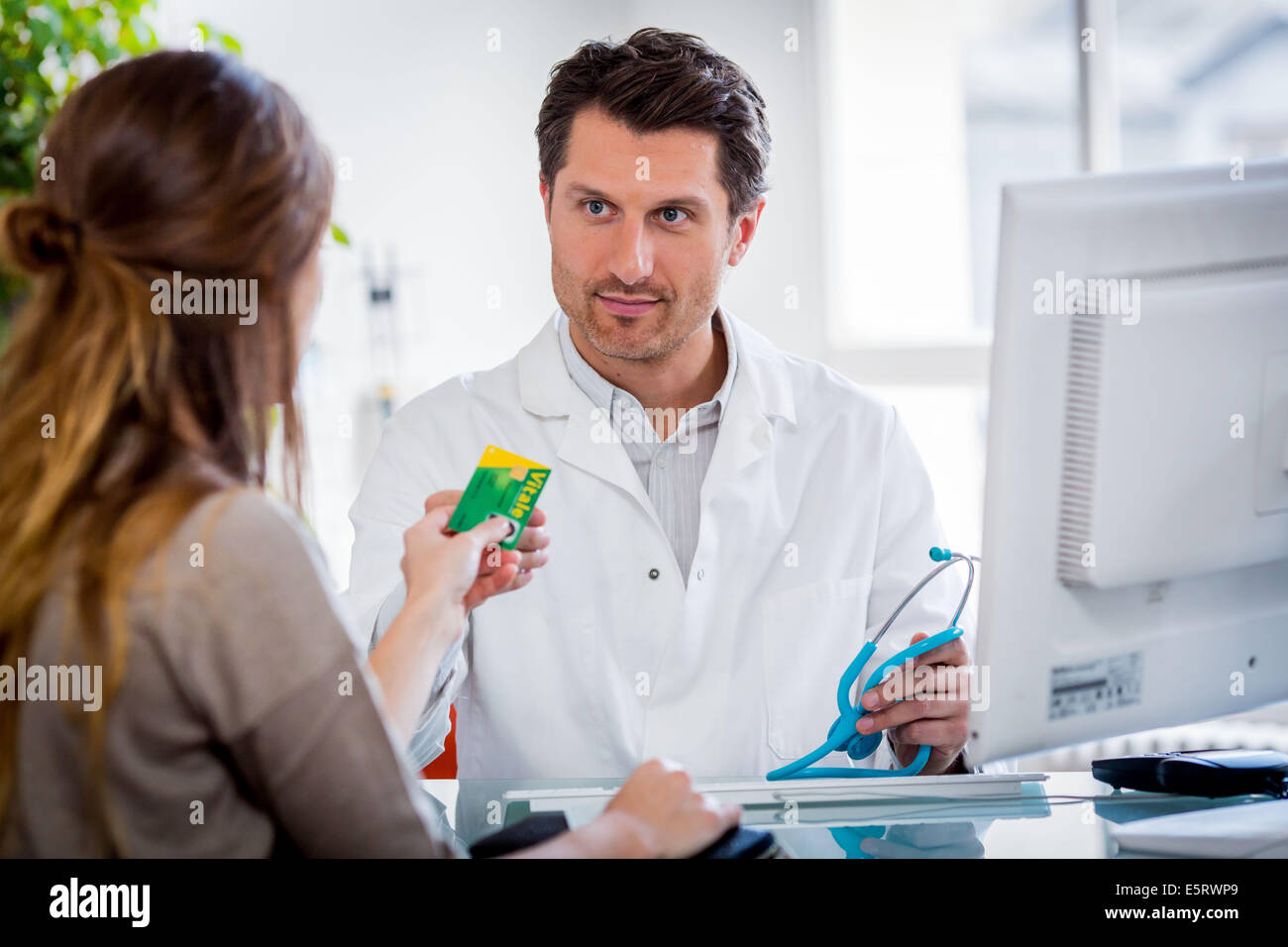 Doctor using the health card of a patient after consultation, The social insurance identity card holds all the administrative - Stock Image