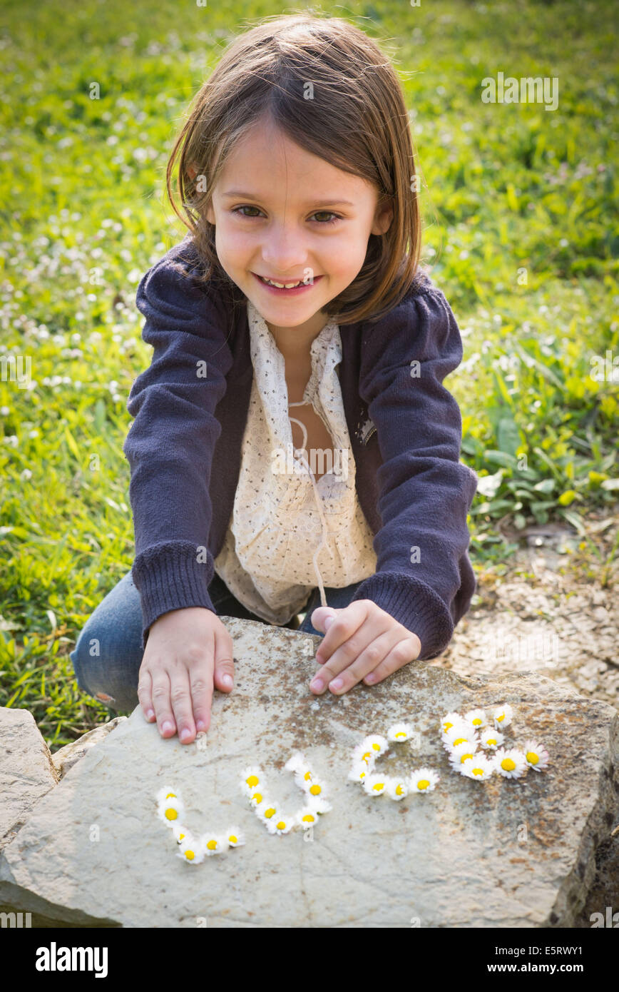 Girl behind her first name written with flowers. - Stock Image
