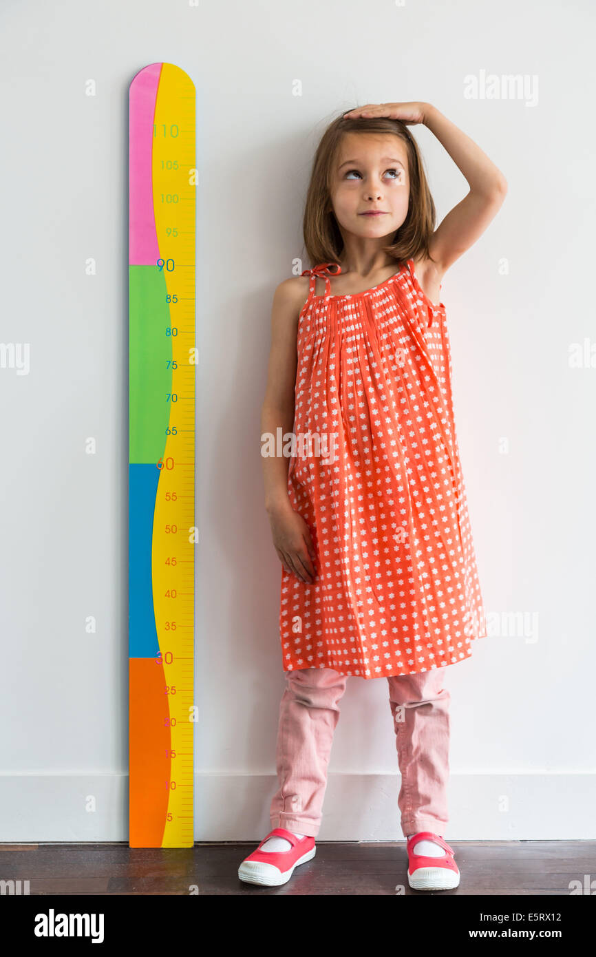 5 year old girl measuring herself with a height gauge stock photo