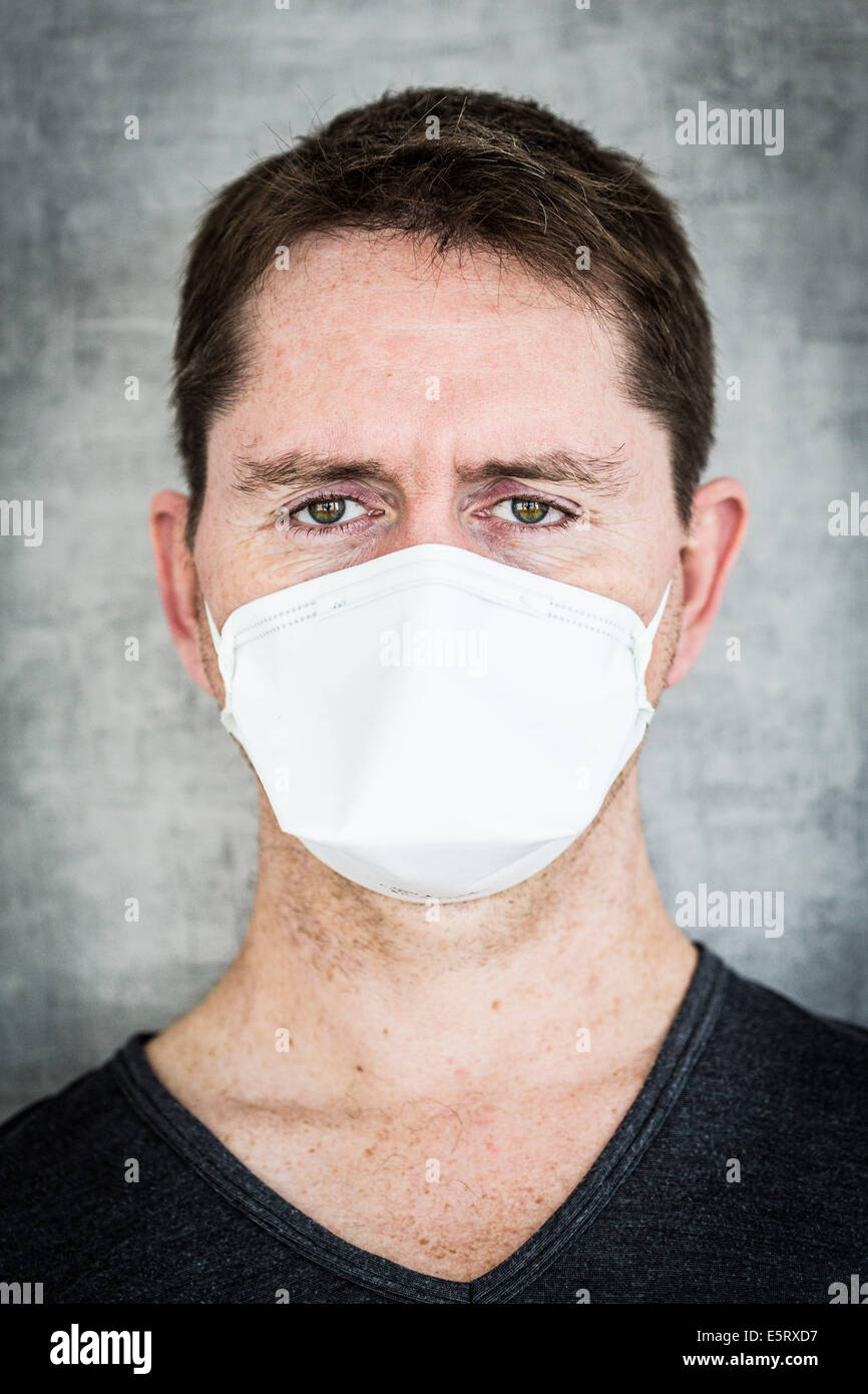 Man wearing a face mask to protect himself from MERS-CoV. - Stock Image
