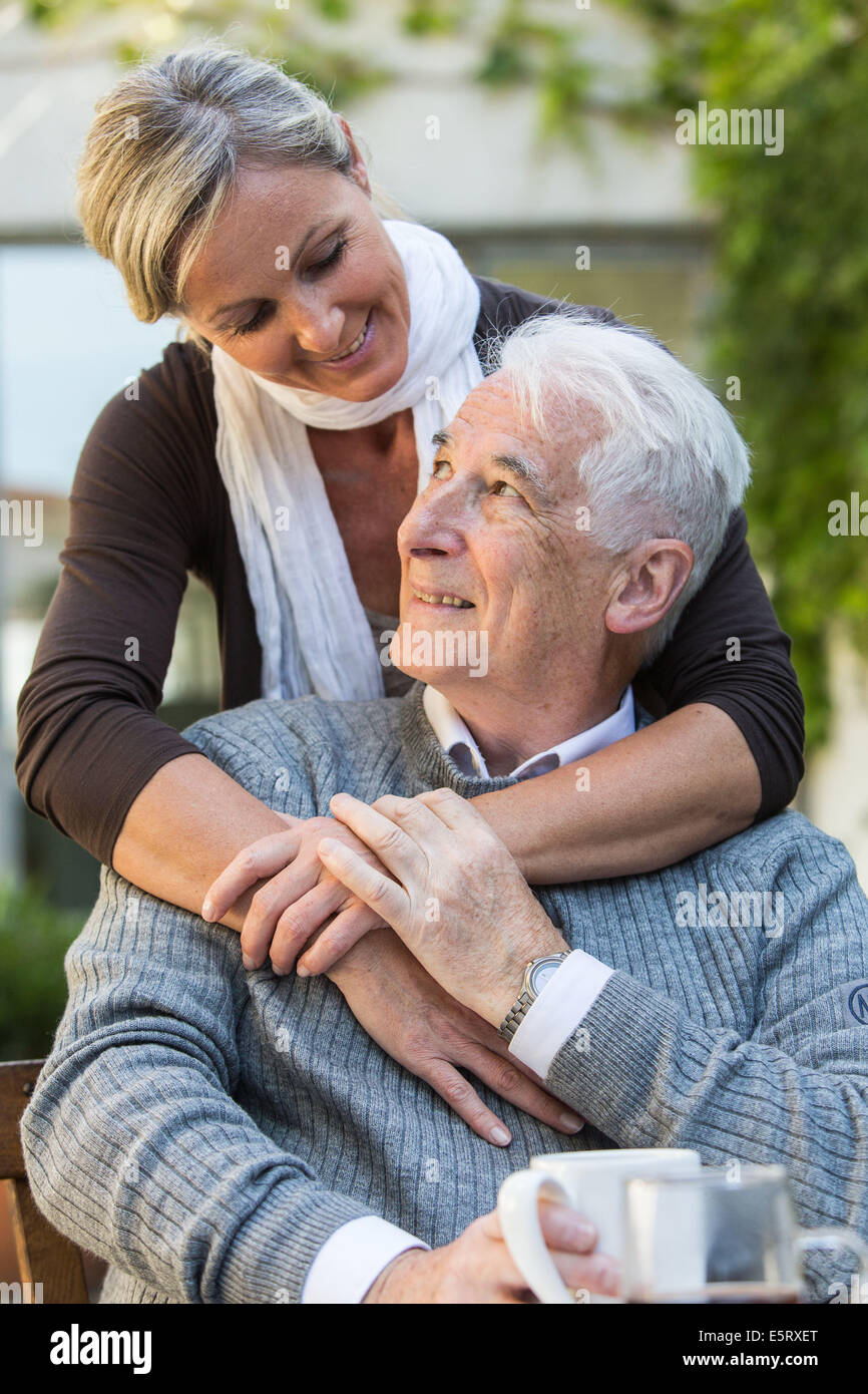 Woman assisting elderly man. - Stock Image