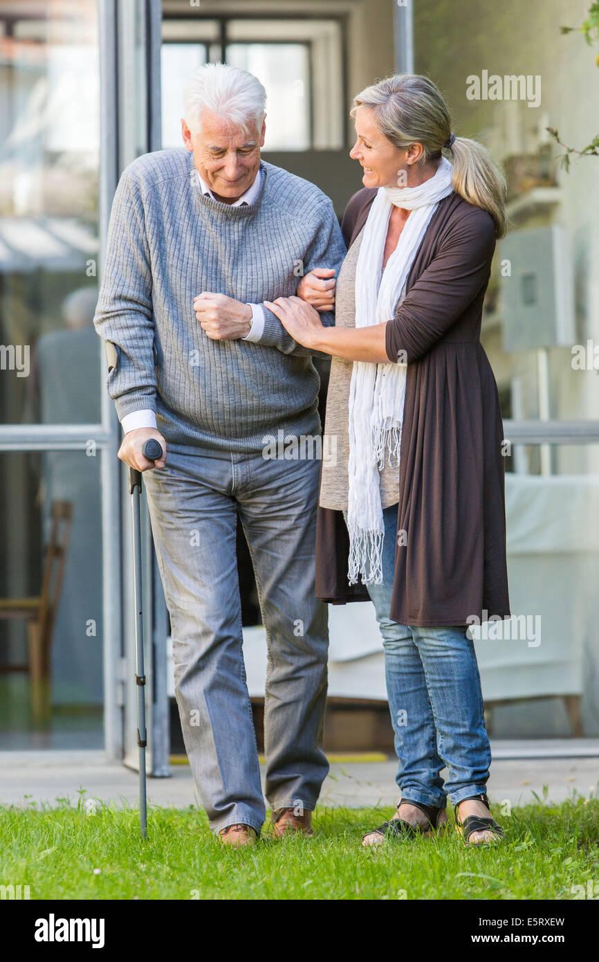 Elderly man walking with crutche. - Stock Image