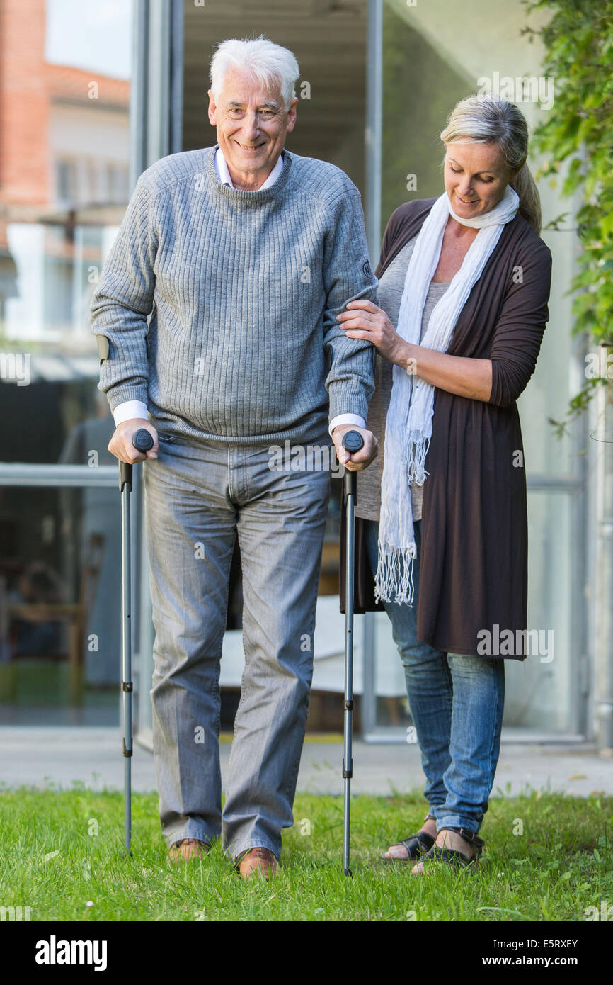 Elderly man walking with crutches. - Stock Image