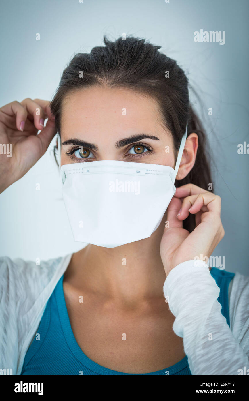 Woman wearing a face mask to protect herself from MERS-CoV. - Stock Image