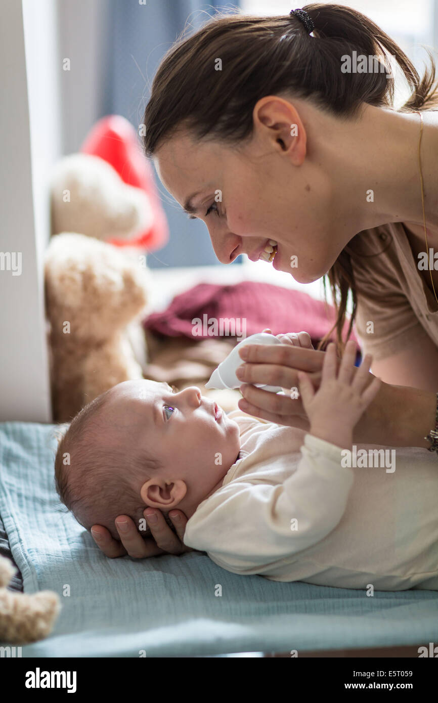 4 months old baby boy having his nose cleared with a nose-blower. - Stock Image