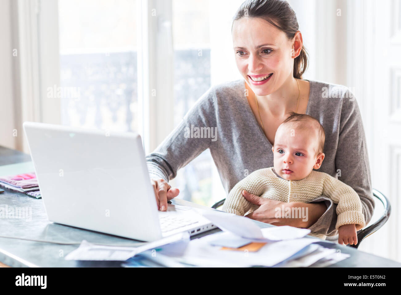 Woman using laptop computer with her 3 month old baby boy. - Stock Image