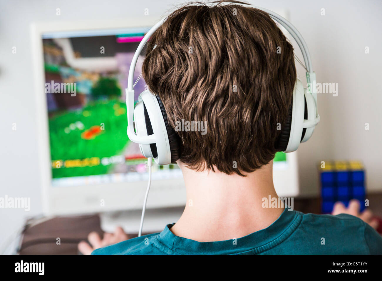 Teenager playing Minecraft multiplayer online game (MMO). - Stock Image