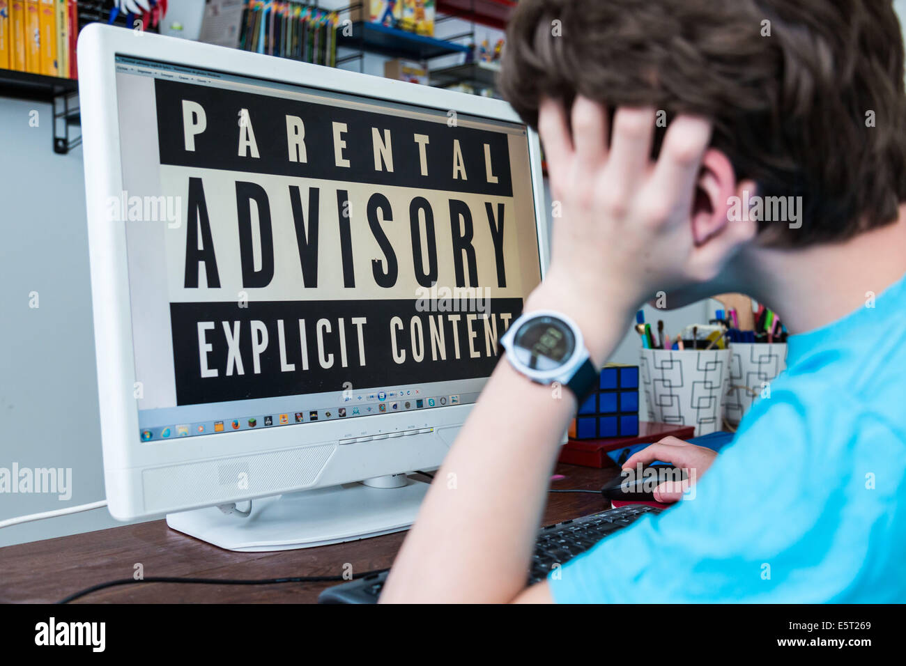 Teenage boy using a computer with a parental control software. - Stock Image