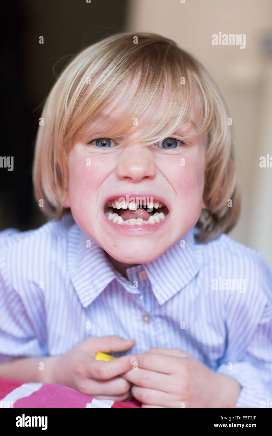 7 year old boy shows a missing tooth and a loose tooth Stock
