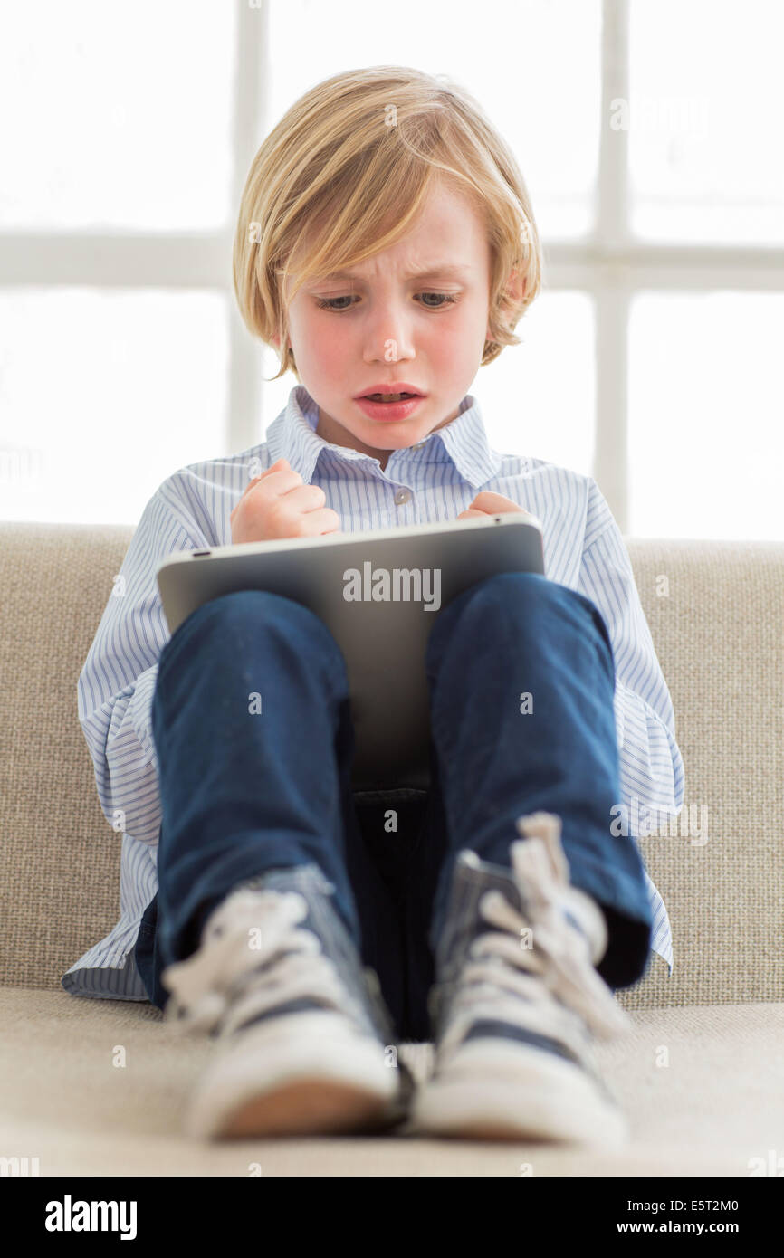 7 year old boy using tablet computer. - Stock Image
