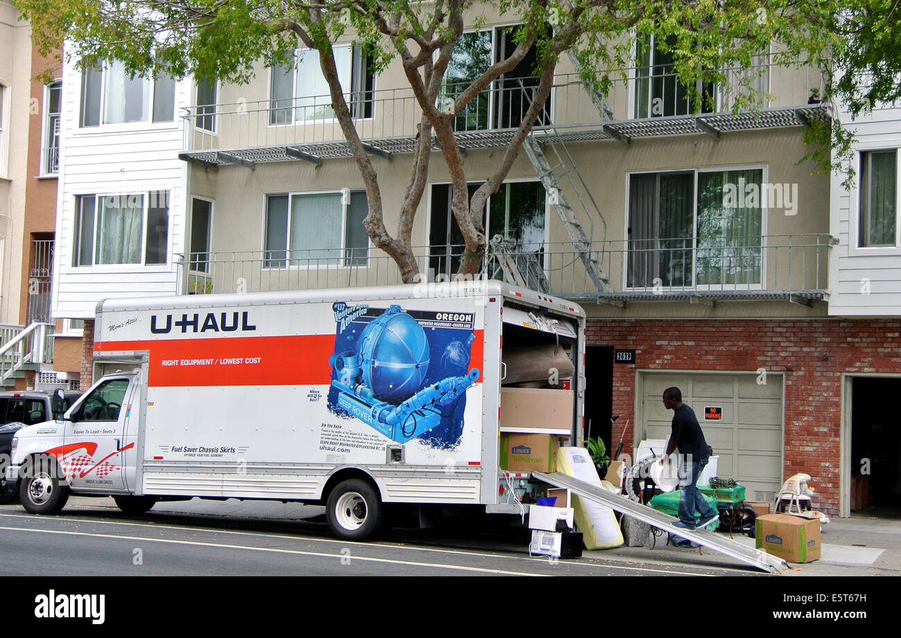 man loads u haul truck with furnishings in front of an apartment building in the Mission District of San Francisco - Stock Image