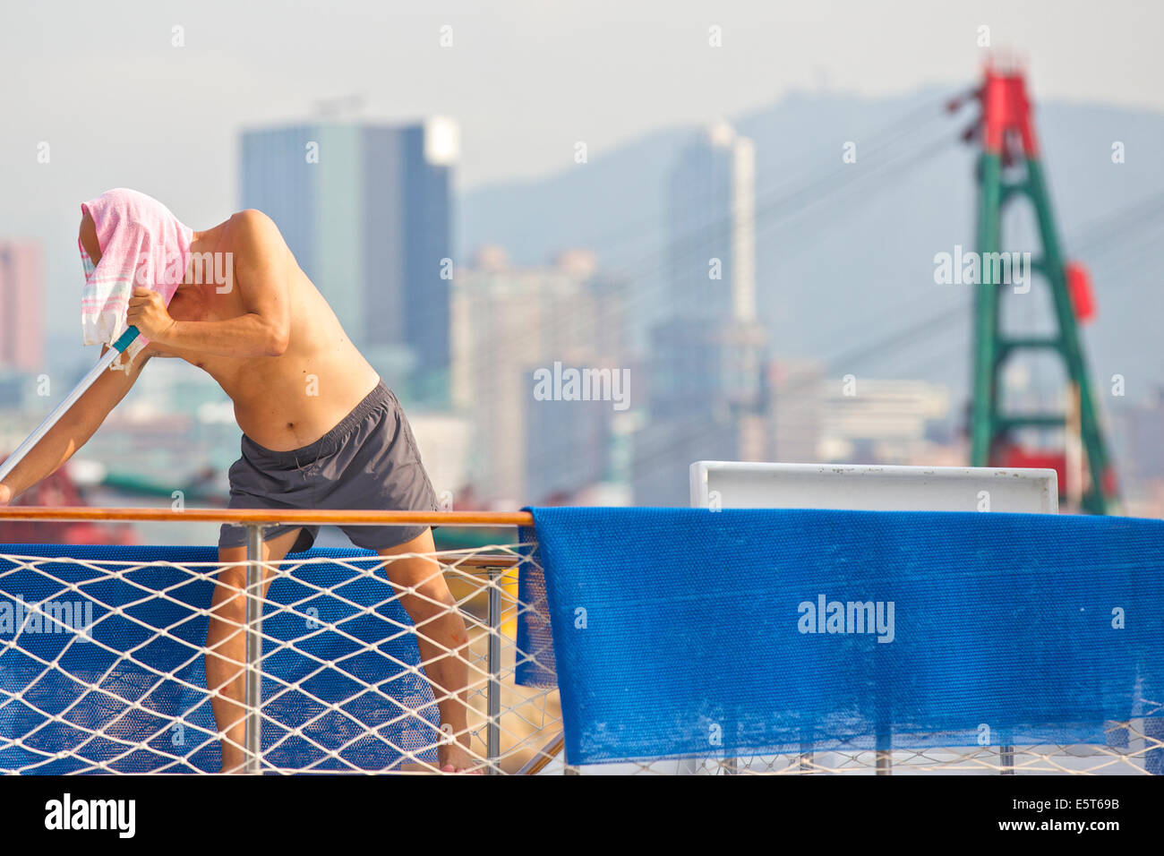 Scrubbing Decks. Chinese Man Cleans The Decks Of A Boat In The Causeway Bay Typhoon Shelter, Hong Kong. - Stock Image