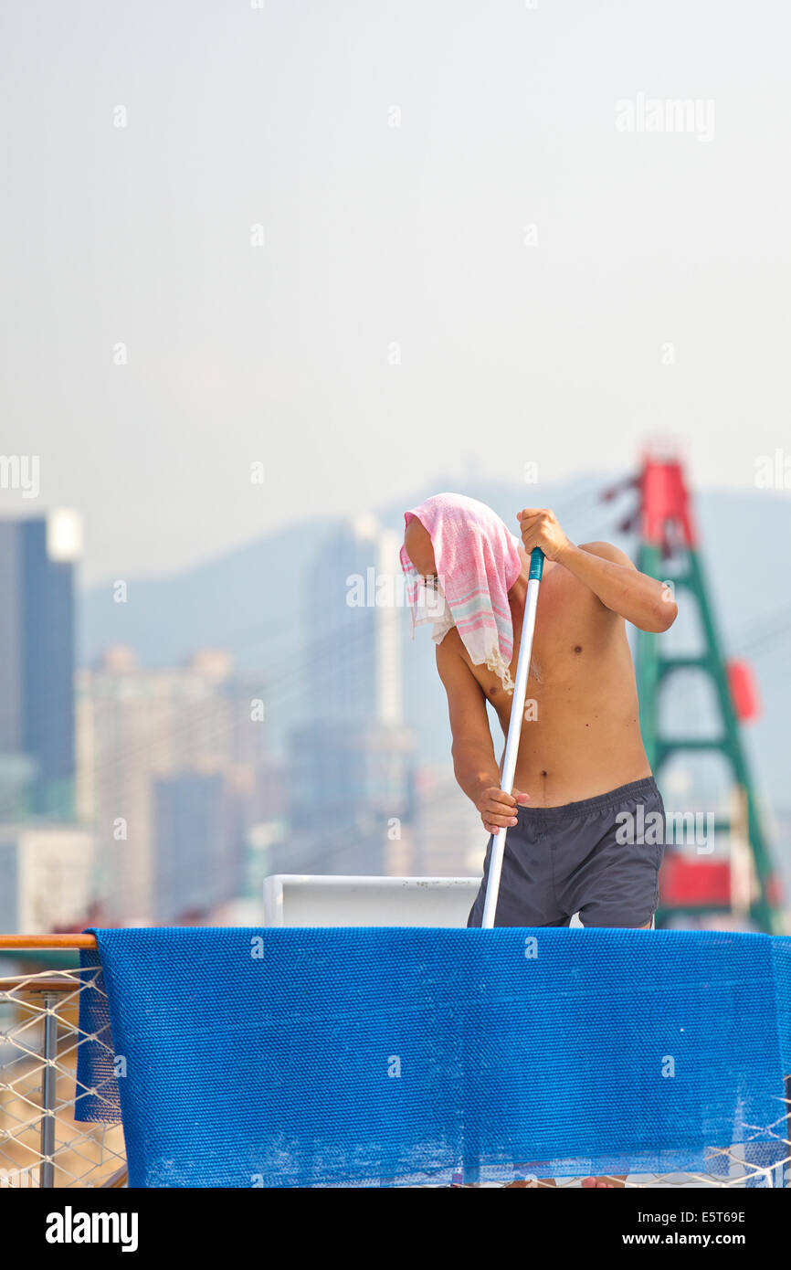 Chinese Sailor Scrubbing The Decks Of A Boat In The Causeway Bay Typhoon Shelter, Hong Kong. - Stock Image
