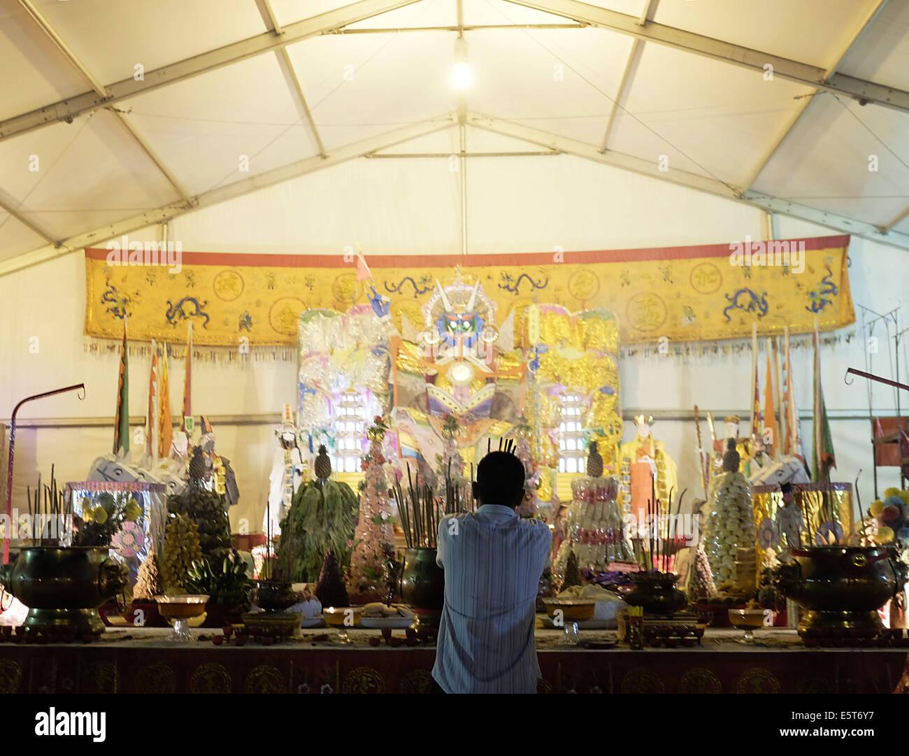 Kajang, SELANGOR, MALAYSIA. 5th Aug, 2014. An Ethnic Chinese devotee handles lit incense sticks during the festive - Stock Image