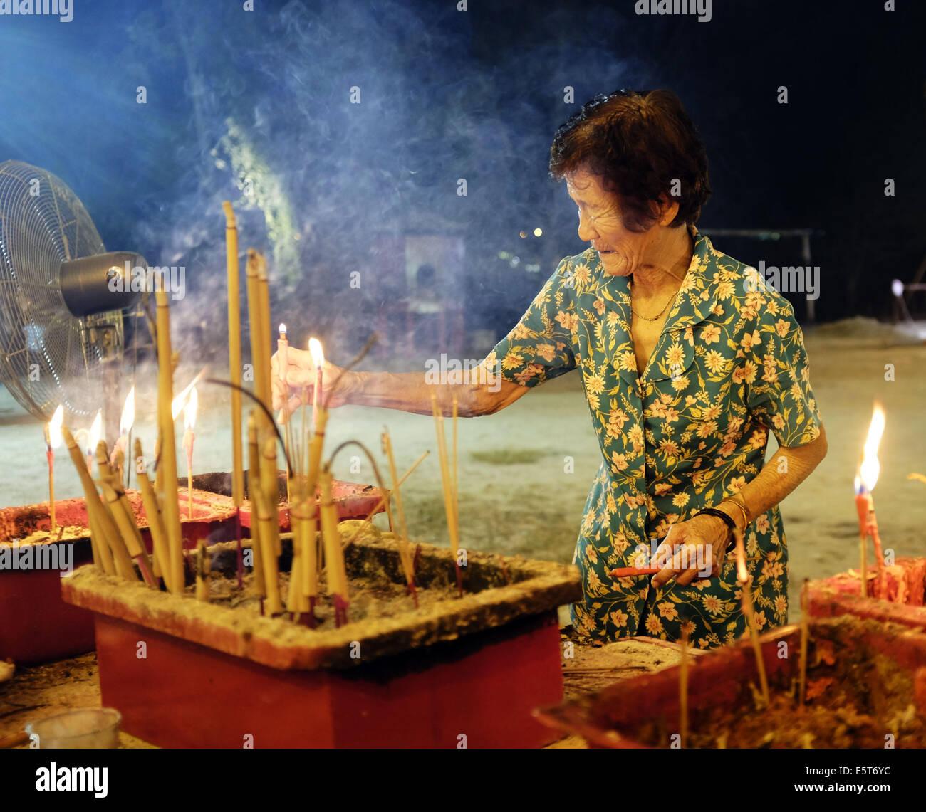Kajang, SELANGOR, MALAYSIA. 5th Aug, 2014. An Ethnic Chinese devotee handles lit incense sticks during the Hungry - Stock Image