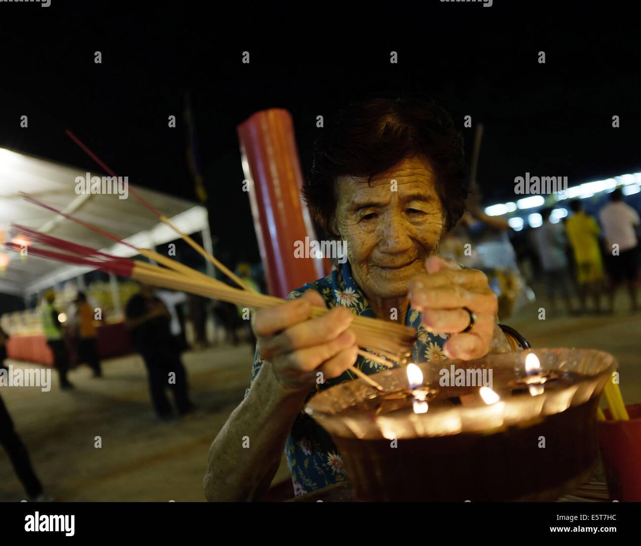 Kajang, SELANGOR, MALAYSIA. 5th Aug, 2014. An Ethnic Chinese devotee lights incense sticks during the festive event - Stock Image