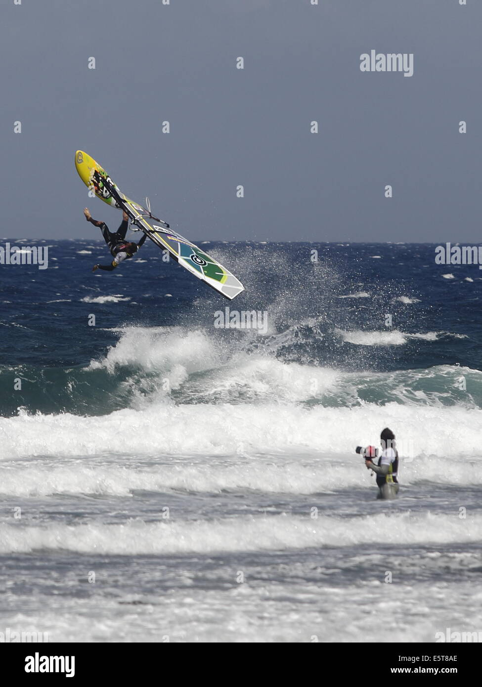 Brazilian windsurfer  Marcilio Browne performing an freestyle aerial manouevre whilst a dedicated photographer looks - Stock Image