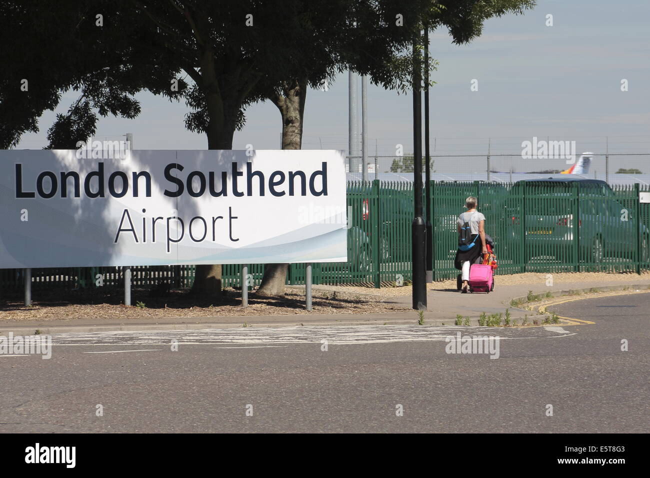 A woman wheeling a suitcase, entering London Southend Airport. - Stock Image